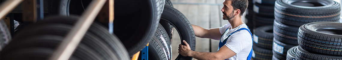 Mechanic picking up a tyre from stock - Tyres St Albans